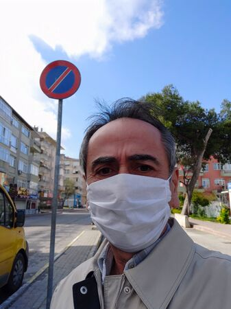 Man in city street wearing face mask protective for spreading of Coronavirus Disease. Portrait of man with surgical mask on face against SARS-CoV-2