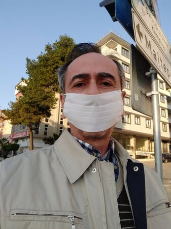 Closeup portrait of sad middle aged man in white surgical mask on the street. Pandemic coronavirus 2020. Quarantine.Virus concept. Epidemic infection
