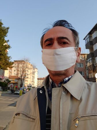 Portrait of man in a surgical bandage on a background of an empty street. Quarantine. Pandemic. Coronavirus. Vaccine.Infection. Medical mask Фото со стока