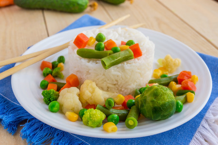 nourish: Rice with vegetables cooked on steam on a white plate, laid out in a circle. Vegan.