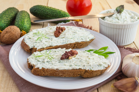 Nutritious sandwich with cottage cheese paste on rye bread on a white plate.
