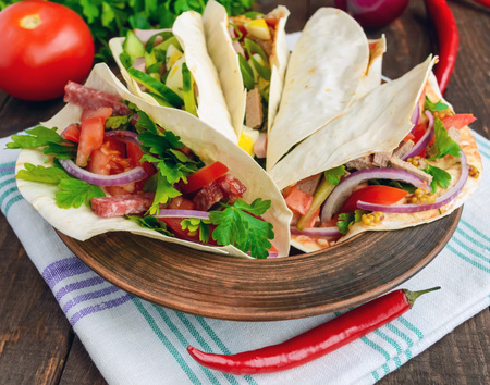 fillings: East pita bread with various fillings (meat, salami, egg, cucumber, parsley, tomato, chili pepper, Dijon mustard). Taco. Stock Photo
