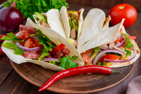 with fillings: East pita bread with various fillings (meat, salami, egg, cucumber, parsley, tomato, chili pepper, Dijon mustard). Taco. Stock Photo