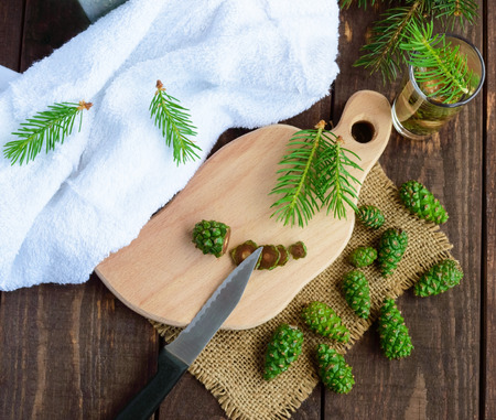 young knife: Young green fir cones on the wooden background. Chopping knife cones for making medicinal infusion. The top view