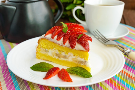 cake decorating: A piece of banana-strawberry sponge cake decorating with mint leaves on a white plate and cup of tea on wooden background