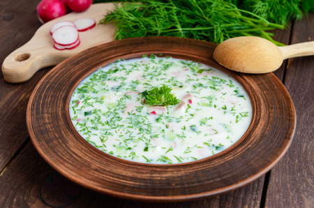 slavonic: Slavonic traditional dish - cold soup okroshka in the yogurt in a clay bowl on a wooden background. Dietary refreshing dish.