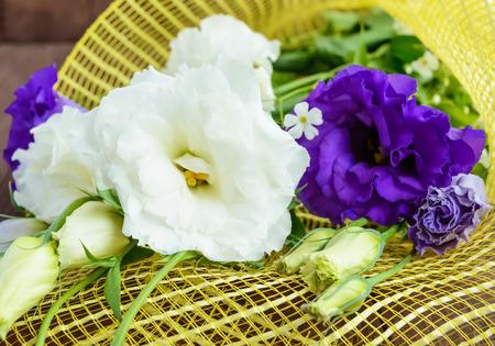 freshly picked: Freshly picked white and purple flowers eustomy (lisianthus)  on the wooden background. Close up Stock Photo