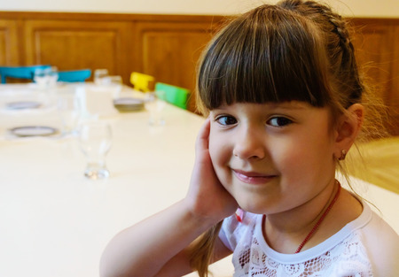 school cafeteria: Little European girl smiling in the foreground, on a background of the dining table. Before the holiday.