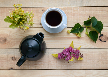 linden flowers: Linden flowers and tea on a light wooden background. Stock Photo