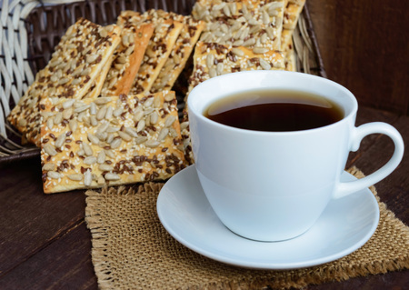 sesame cracker: Dietary crunchy cracker with cereals (sunflower seeds, flax and sesame) and a cup of tea on a dark wooden background. Stock Photo