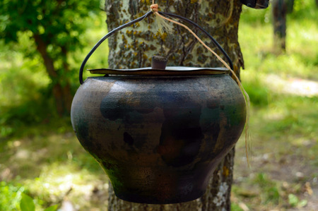 A pot for cooking over an open fire, hanging on the tree. For hikes. Mens style.