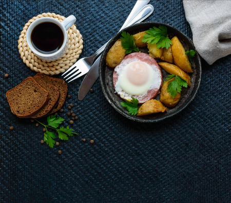 submission: Fried egg in salami and baked potatoes. Submission of a frying pan with a cup of coffee and rye bread. Breakfast. The top view