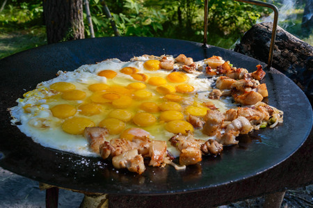 cook griddle: Fried eggs with pieces of pork on a large flat pan, cooking outdoors. Stock Photo
