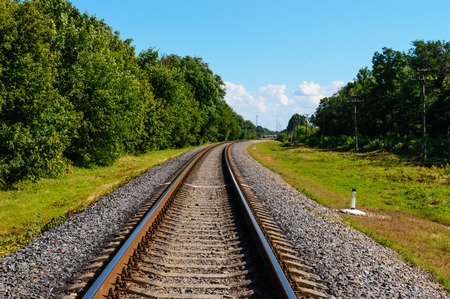 forest railway: The railway goes to horizon, on both sides of the green dense forest. Stock Photo