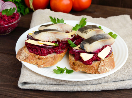 meatless: Meatless dietary sandwich: boiled beetroots, purple onion, salted herring and flakes of smoked cheese on a crispy baguette