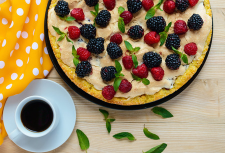 Pie (Tart) with fresh blackberries and raspberries, air meringue, decorative mint and cup of coffee Stock Photo