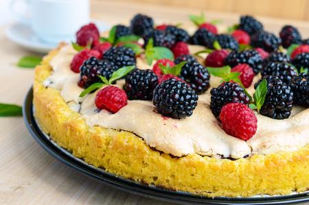 Pie (Tart) with fresh blackberries and raspberries, air meringue, decorative mint. Close up Stock Photo