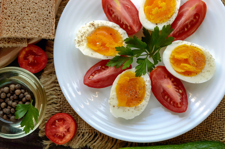 light diet: Boiled egg and fresh tomato, black bread - light diet breakfast. The top view