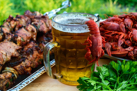 Foamy beer in a glass and boiled crawfish, grilled meat on skewers in the background. For the holidays, enjoying the outdoors. Stock Photo