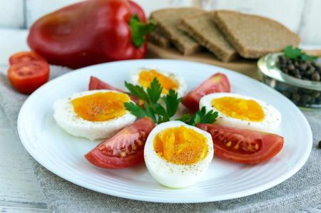 light diet: Boiled egg and fresh tomato, black bread - light diet breakfast. Close up Stock Photo