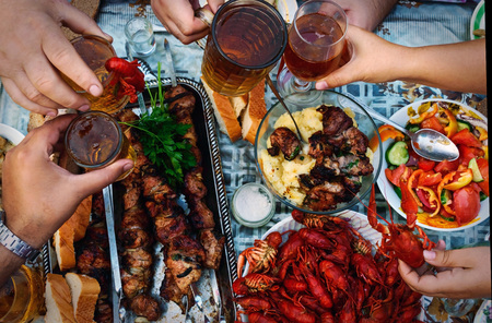 dine: Feast of beer, meat skewer and crayfish. The top view on the group of people who dine outdoors. Stock Photo