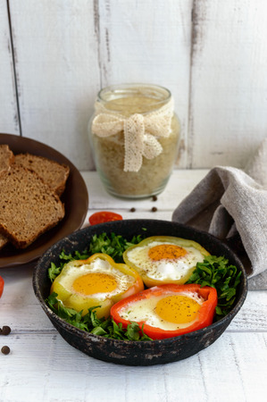light diet: Fried egg in the ring of the bell peppers with herbs and brown bread - light diet breakfast. Stock Photo