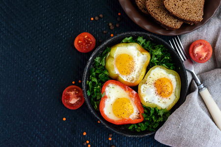 light diet: Fried egg in the ring of the bell peppers with herbs and brown bread - light diet breakfast. The top view.