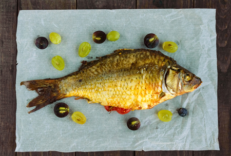 stuffed fish: Baked fish carp, stuffed bell peppers and grapes. The top view.