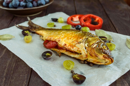 stuffed fish: Baked fish carp, stuffed bell peppers and grapes. Stock Photo
