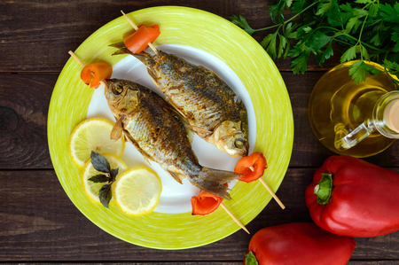 Fried fish (carp) on skewers with pieces pepper and lemon. The top view