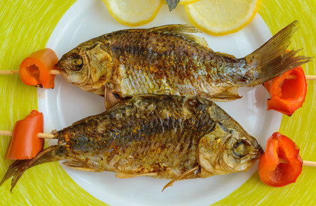 Fried fish (carp) on skewers with pieces pepper and lemon. The top view. Close up