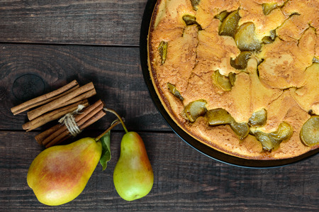 home baked: Home baked biscuit flavored pear charlotte cake with cinnamon. On a dark wooden background. The top view. Stock Photo