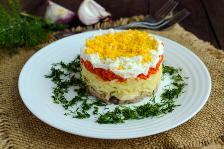 Easy Diet salad layers in the shape of a circle (tuna in oil, boiled potatoes, carrots, eggs). Alternative Slavonic traditional dish Mimosa.