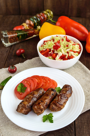 Juicy grilled rolls of minced meat wrapped in bacon with fresh tomato and a light salad of Chinese cabbage and bell pepper. Stock Photo