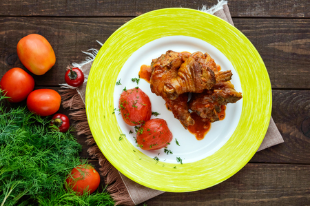 without legs: Chicken legs with tomato sauce and marinated tomatoes without skins in their own juice. The top view. Stock Photo
