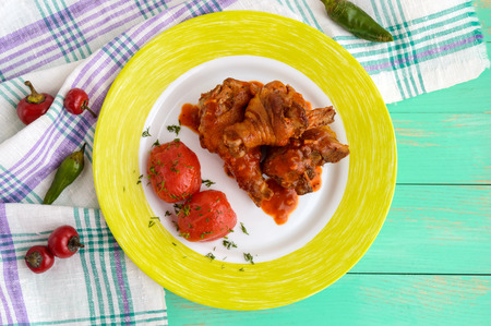 Chicken legs with tomato sauce and marinated tomatoes without skins in their own juice. The top view. Stock Photo