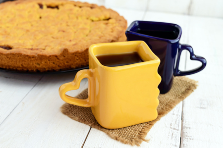 Two beautiful cups (dark blue and yellow) with coffee, tea and freshly baked homemade cake with apricot jam.