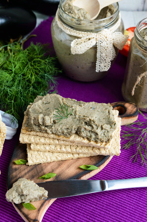 put on: Gentle paste, paste from the eggplant. Dietary dish. Put on a crisp low-calorie diet fitness bread. Vegan cuisine. For picnic. Stock Photo