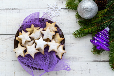 Green fir branches with star-shaped cookies on a white background. Christmas theme. The top view.