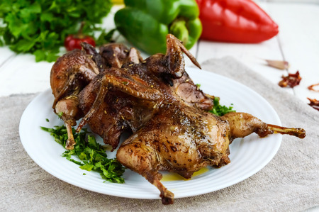 spit: Roasted quail. Serving on a plate with greens. Close-up. Holiday menu. Stock Photo