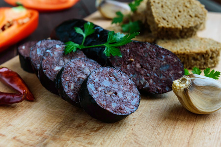 Morcillo (Spanish black pudding, blood sausage), cutting slices, black rye bread in a heart shape, pepper, garlic on a wooden board. Close up. A festive meal on Christmas, Easter
