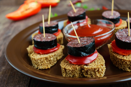 Sandwiches with black rye bread in the shape of a heart, blood sausage (Morcillo) and pieces of sweet pepper on skewers in a ceramic bowl with tomato sauce on a dark wooden background.  Close up