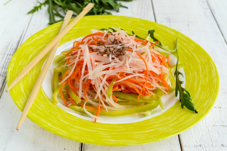 Fresh diet fitness salad of daikon radish, carrots, flax seeds, arugula. Vegan cuisine. Close up Stock Photo
