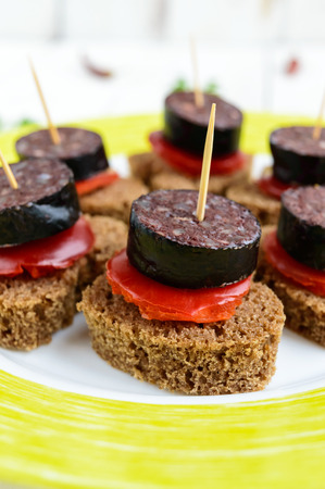 Sandwiches with black rye bread in the shape of a heart, blood sausage (Morcillo) and pieces of sweet pepper on skewers and tomato sauce, on a white wooden background. Close up