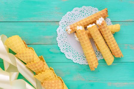 tube top: Tender honey wafers in the form of tubes, stuffed with air cream on white lace napkin. The top view