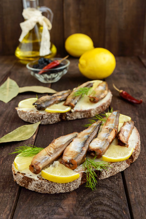 Sandwich with smoked fish capelin (sprats), lemon on black rye bread. Snack on a dark wooden table.