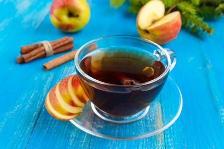 Winter warms festive Vitamin tea with apple and cinnamon on a blue wooden background in a transparent cup of glass.