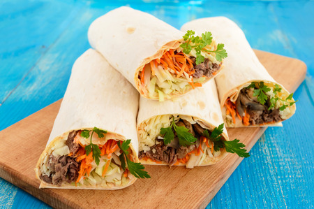 filled roll: Shawarma sandwich - fresh roll of thin lavash (pita bread) filled with grilled meat, mushrooms, cheese, cabbage, carrots, sauce, green. Traditional Eastern snack. On a blue wooden background.