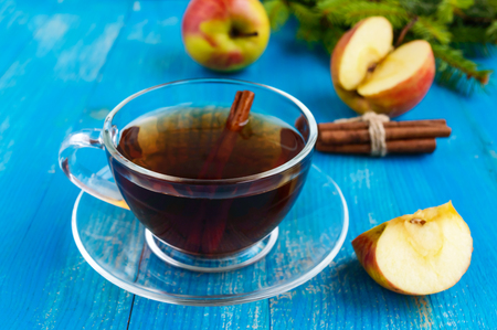 warms: Winter warms festive Vitamin tea with apple and cinnamon on a blue wooden background in a transparent cup of glass.