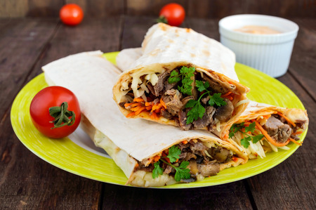 filled roll: Shawarma sandwich - fresh roll of thin lavash (pita bread) filled with grilled meat, mushrooms, cheese, cabbage, carrots, sauce, green. Traditional Eastern snack. On a dark wooden background. Stock Photo